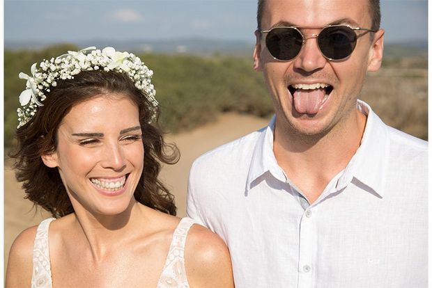 A candid shot of a bride and groom on a beach pulling funny faces.