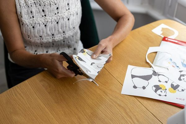 A woman uses a pair of scissors to cut around an iron-on transfer design.