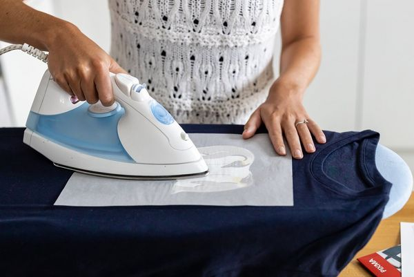 A woman irons an iron-on transfer onto a dark t-shirt.
