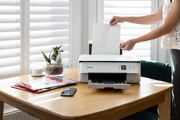 A woman loads a sheet of iron-on transfer paper into a Canon PIXMA TS5350 printer.