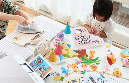 A child sits at a table which is covered with papercraft materials.