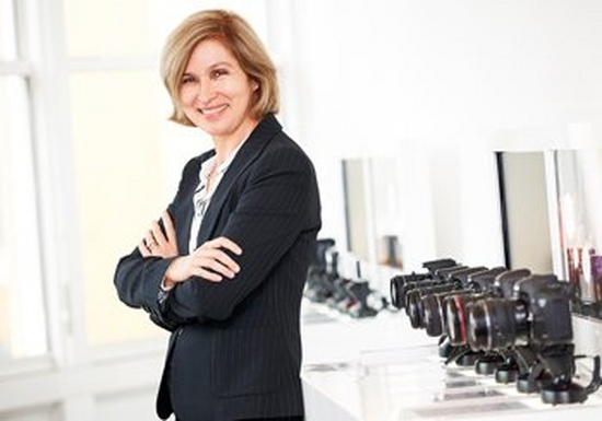 Caroline Serfass, Senior VP and CIO, Canon Europe, smiling with her arms folded.