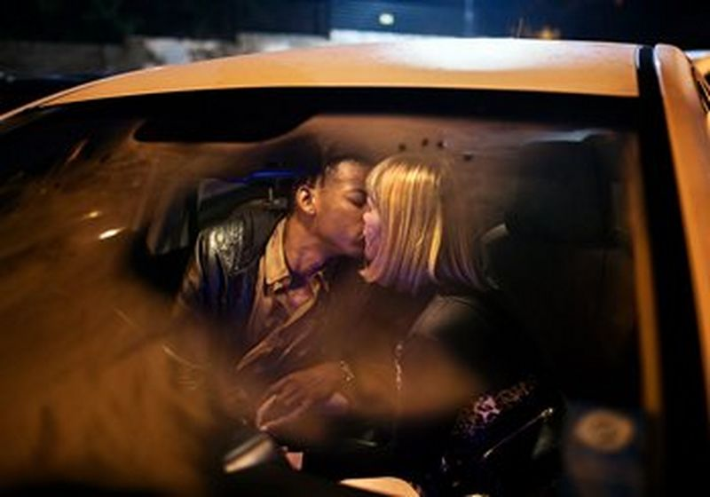 A couple kissing in a car. The windscreen slightly steamed.
