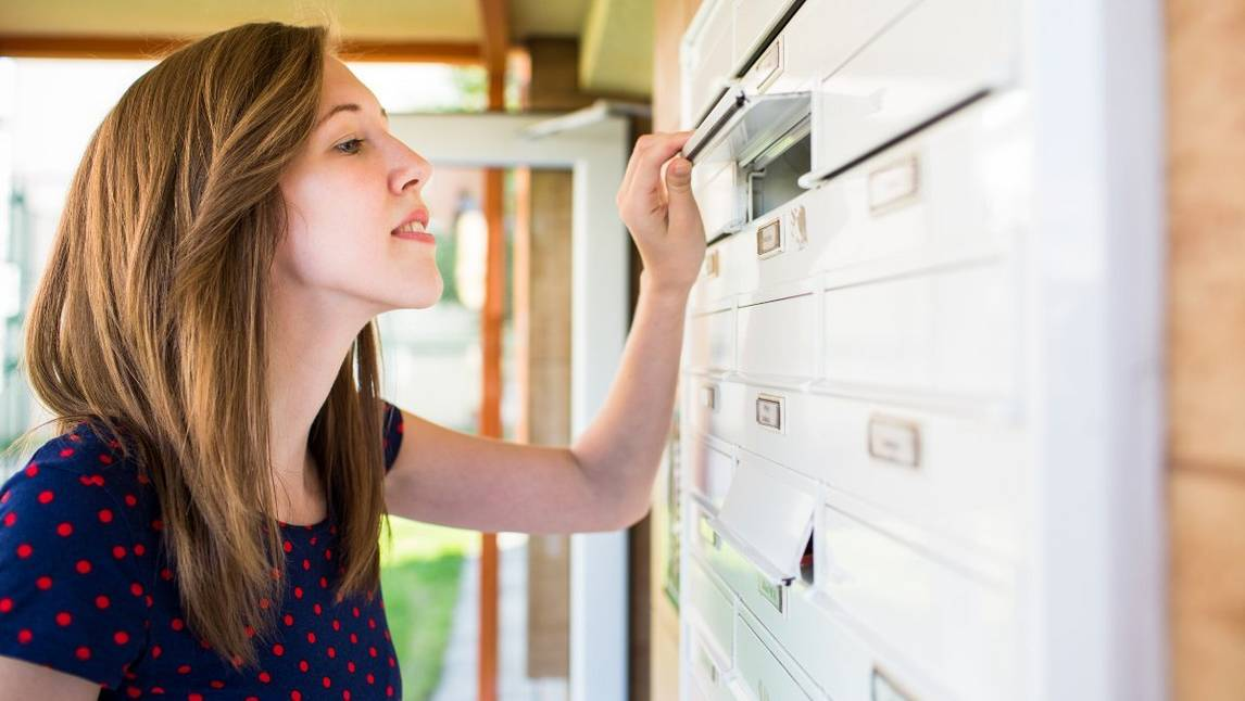 Woman looking into postbox in shared mail area