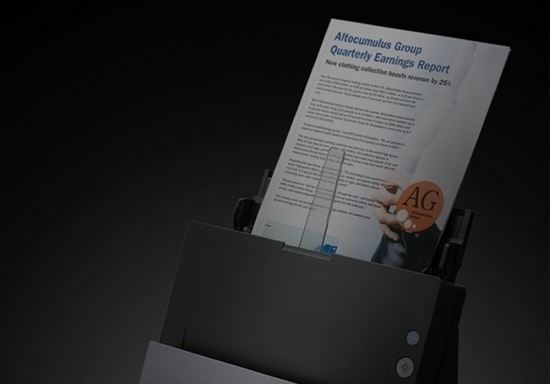 A company's quarterly earnings report is put through a document scanner, contrasted with a black background.