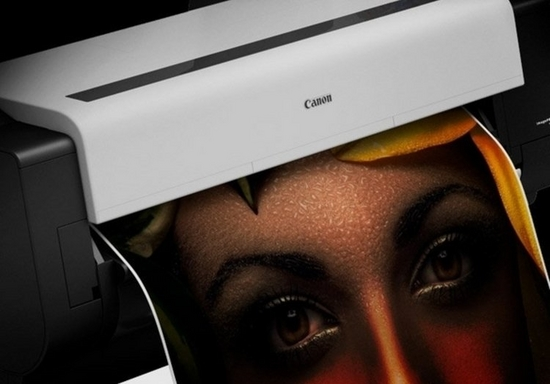 Close-up of a wide format Canon printer printing a sheet of paper with a woman's face.