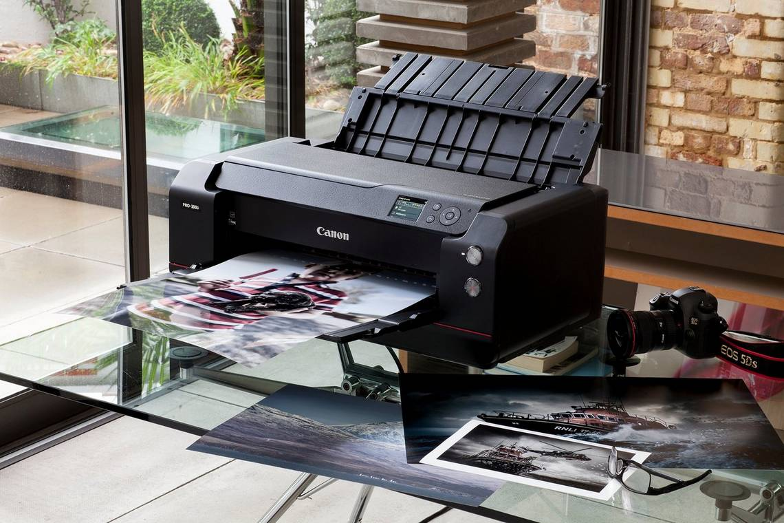 A Canon imagePROGRAF PRO-1000 printer and Canon camera on a glass table surrounded by prints.