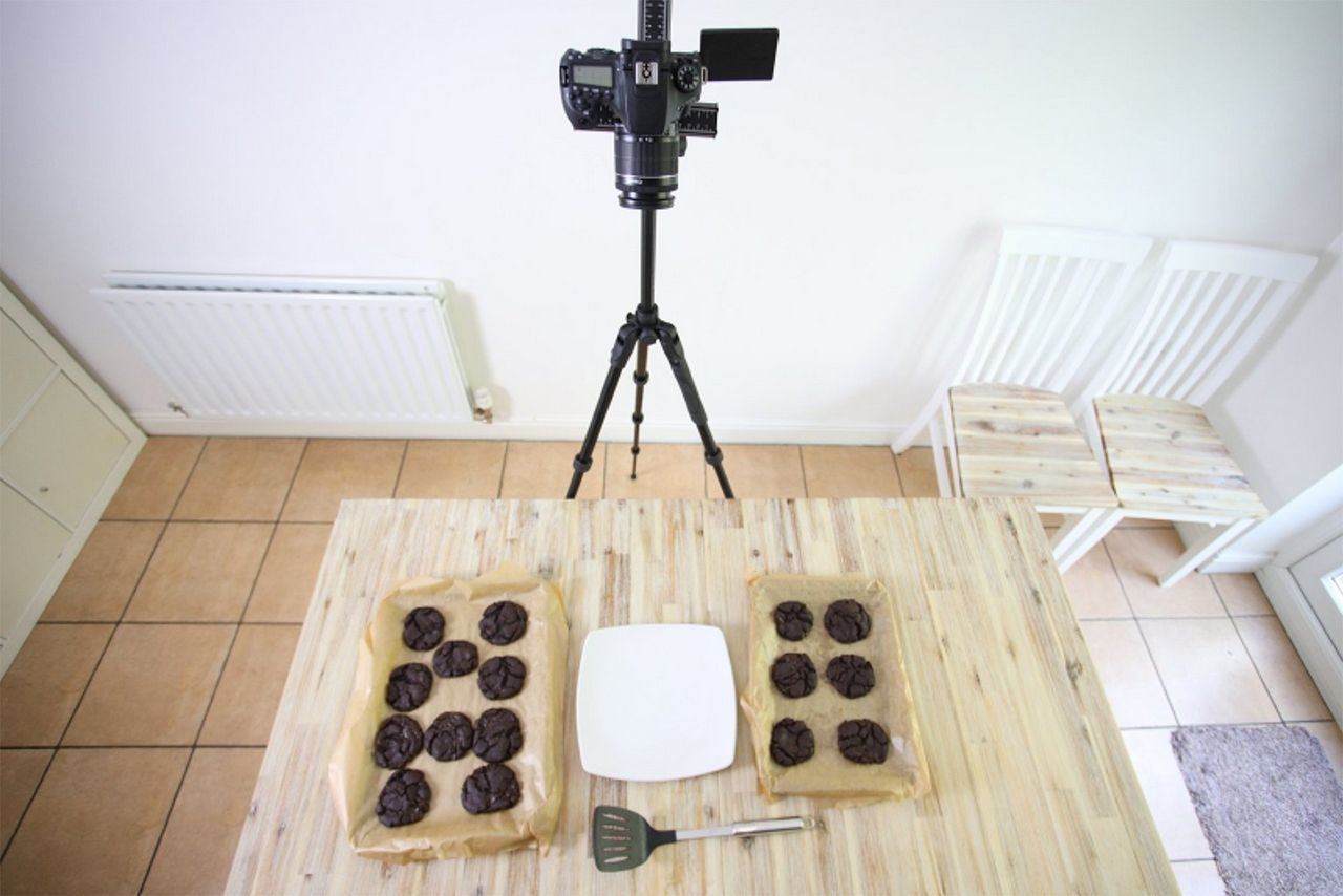 A Canon EOS 90D on a tripod filming cookies cooling on trays.
