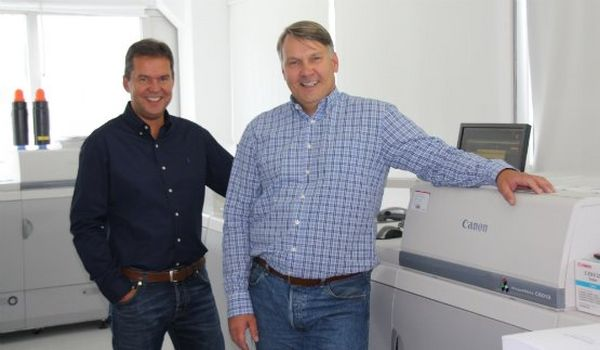 Two print service providers standing in front of a Canon production printer