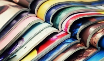 Colourful magazines opened stacked on top of eachother