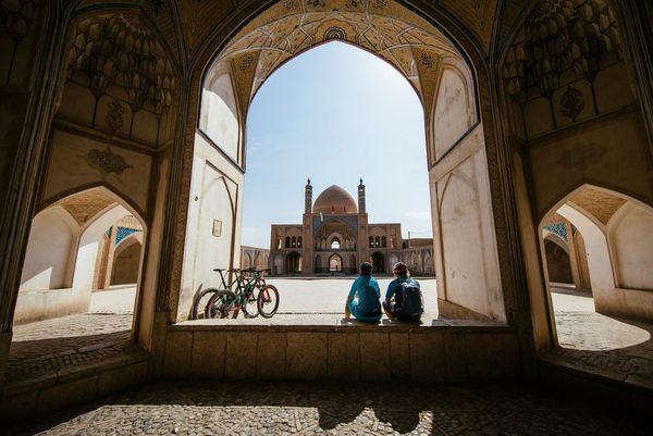 Two mountain bikers sit with their backs to the camera in an archway in front of a mosque. Photo by Martin Bissig.