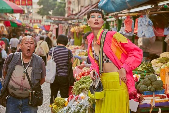 A fashion model in a bright yellow skirt and a fluorescent pink jacket poses at a busy market, while an open-mouthed man walks alongside her.
