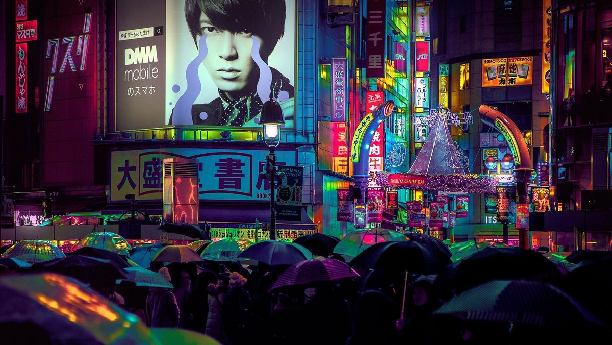 A crowded sea of umbrellas at a busy, neon-lit intersection in the heart of Tokyo as people cross the road at night.