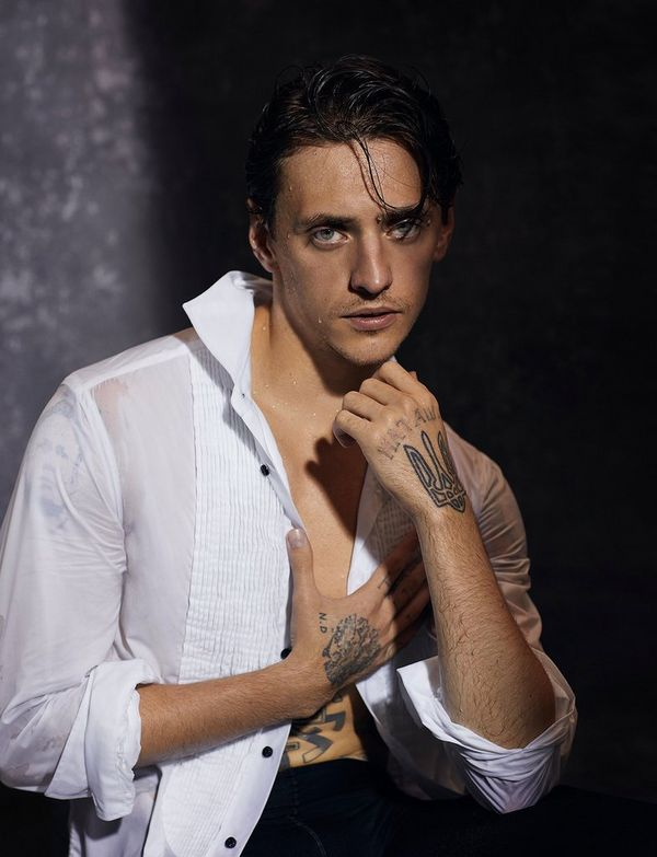 Sergei Polunin gazes into the camera in this portrait, his chin resting on one hand, with his other hand holding together his unbuttoned, wet white shirt – distinctive tattoos visible on both hands.