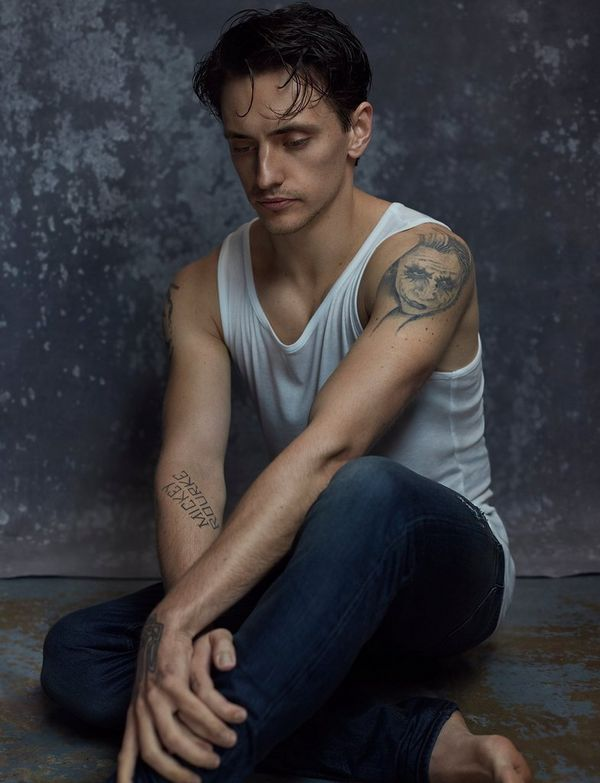 Dressed in a white vest and dark jeans, dancer Sergei Polunin sits with his arms pulled together, looking down at the ground in a portrait by Lorenzo Agius against a grey backdrop.