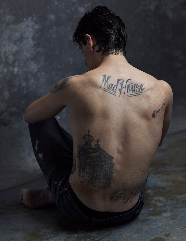 Dancer and actor Sergei Polunin is photographed sitting topless against a grey backdrop, showcasing his array of tattoos, including the large script Mad House at the top of his back.