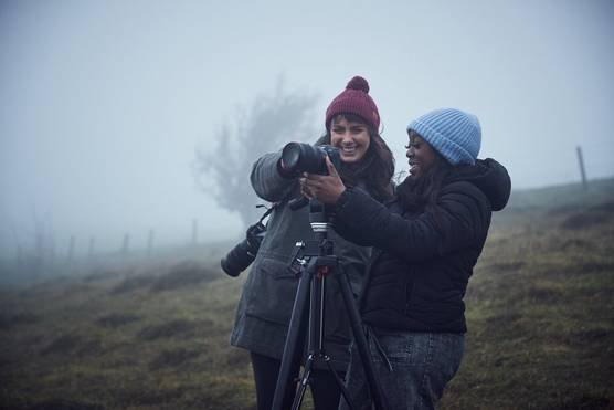 Two women, both wearing winter clothing, on a foggy hillside, adjusting a Canon camera on a tripod.