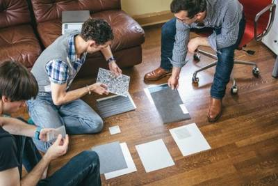 Three men sitting on the floor looking at rectangles of patterned material