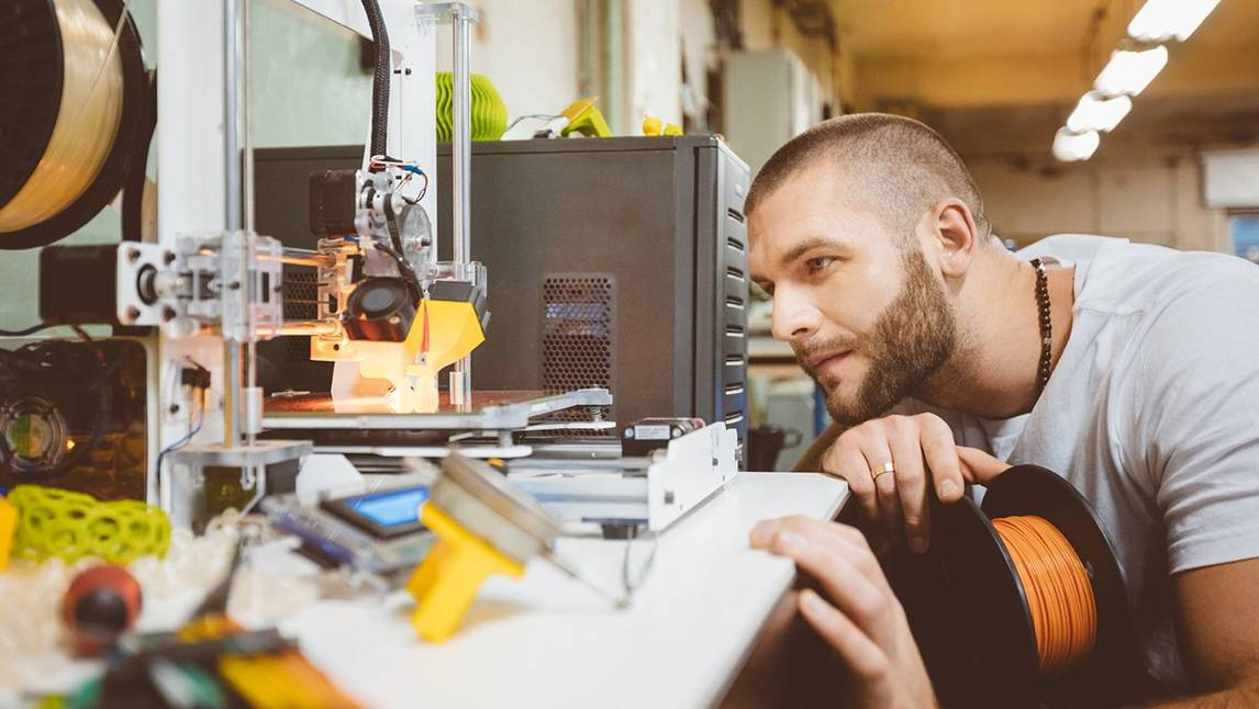 male-looking-at-3D-printer-in-constuction-shop