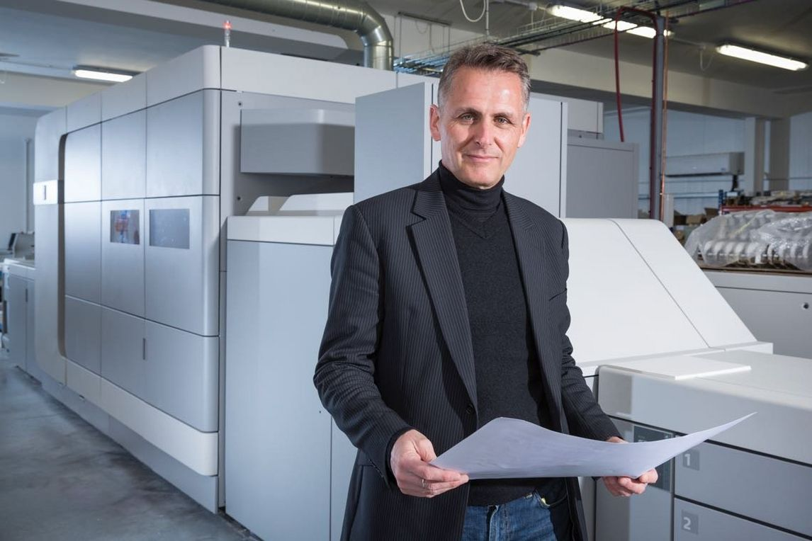 Man stands front of varioprint i300 digital printing press holding large piece of paper
