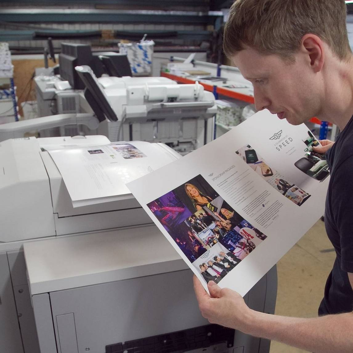 Man examines pages of photo prints from commercial printer