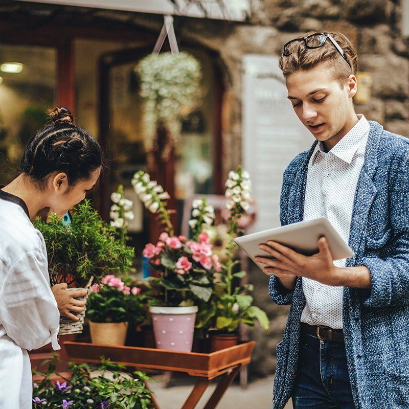 man looking at tablet while shopping at a florist