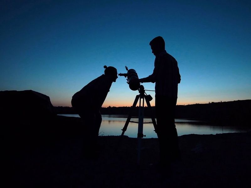 Man looking through telescope at sunset with a friend