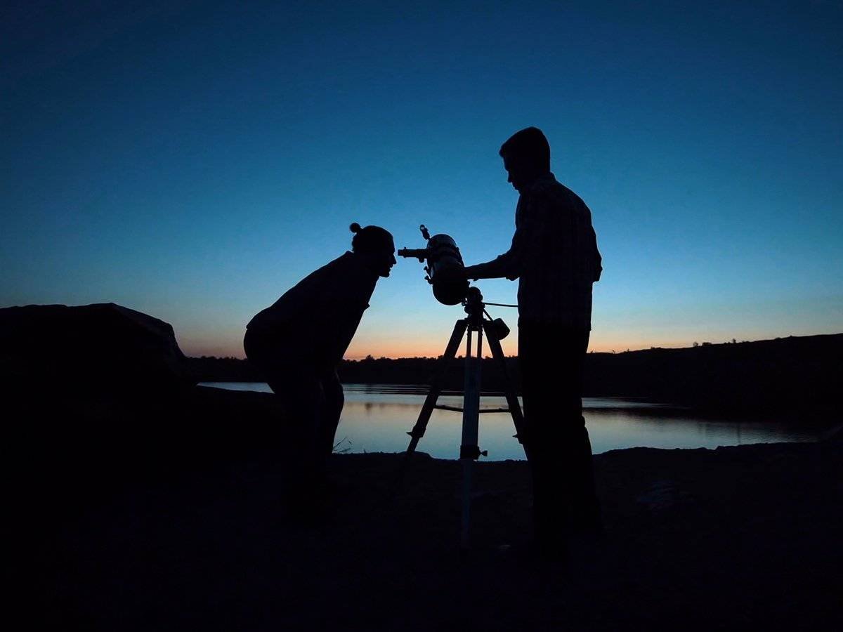 man looking through telescope at sunset