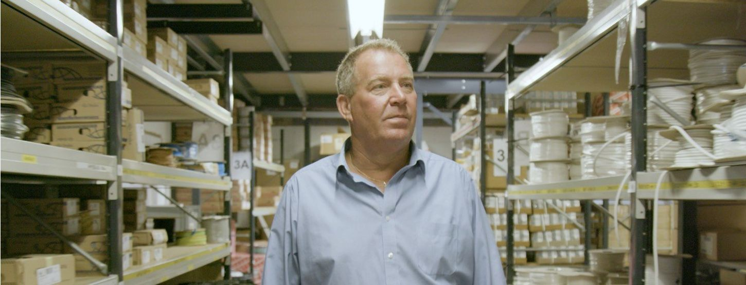 Middle-aged man in shirt walks between warehouse shelving
