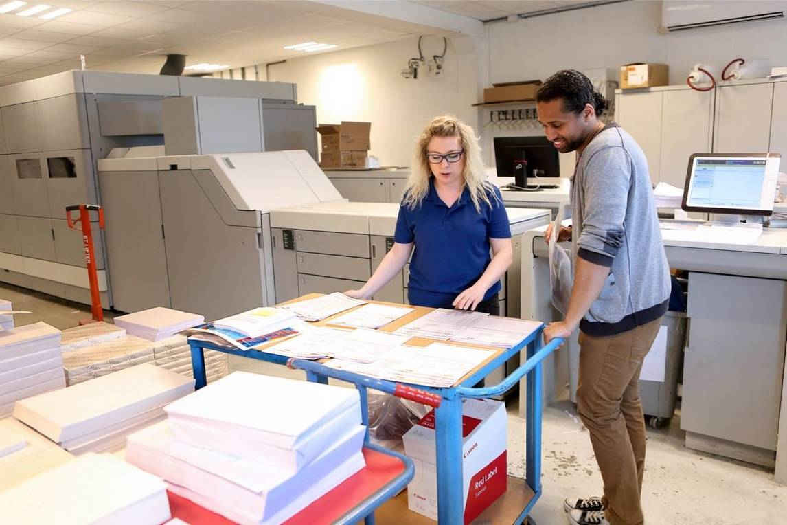 Woman and man in front of large inkjet production printers, examining book pages to be printed