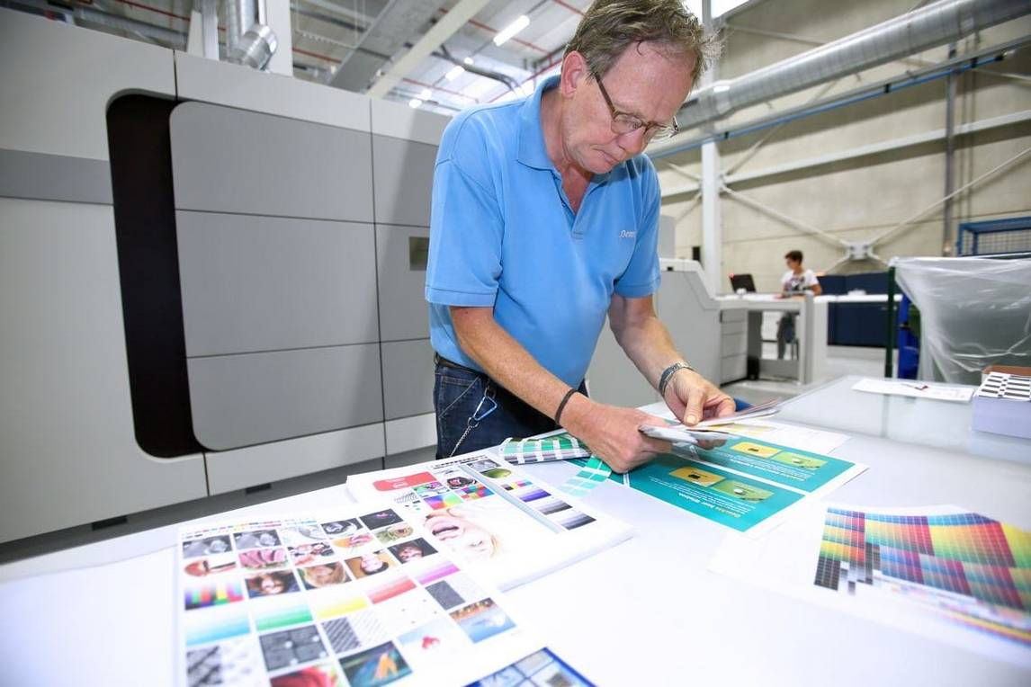 Man examines colour digital prints for book printing