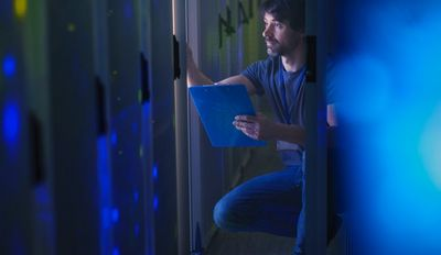 Blue-tinged view of a man in jeans and T-shirt referring to a clipboard while checking an IT data centre.