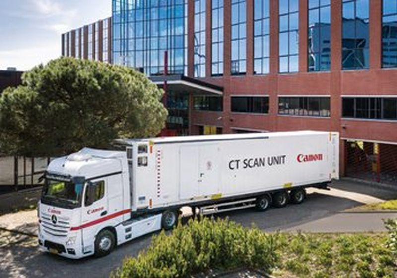 A Canon branded lorry parks a mobile CT scanning unit, with CT SCAN UNIT and the Canon logo printed on the side. It is outside what appears to be a brown brick office building, surrounded by trees and bushes.