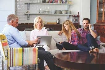 Family sitting in living room on digital devices