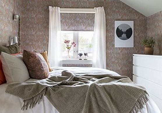 A recreated 18th century wallpaper with patterns of Lily of the Valley is used in a modern bedroom interior.