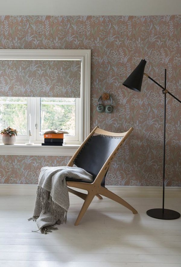 A chair, with clothing draped across it, and a simple downward facing floor lamp, set against the reproduction wallpaper with Lily of the Valley pattern.