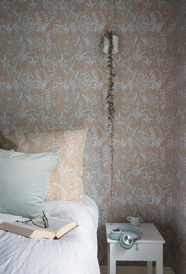A partial view of a bed with a bedside table, set against the reproduction wallpaper with Lily of the Valley pattern.