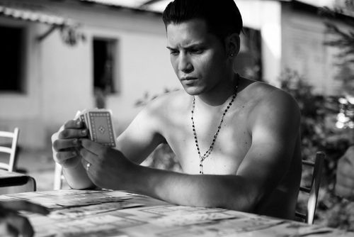 Life in low light - Man with no shirt playing cards - taken with a EOS 5D Mark IV