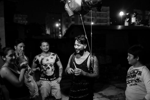 Life in low light - B&W Image - Man with ballons amongst a group of people all laughing - taken with a EOS 5D Mark IV
