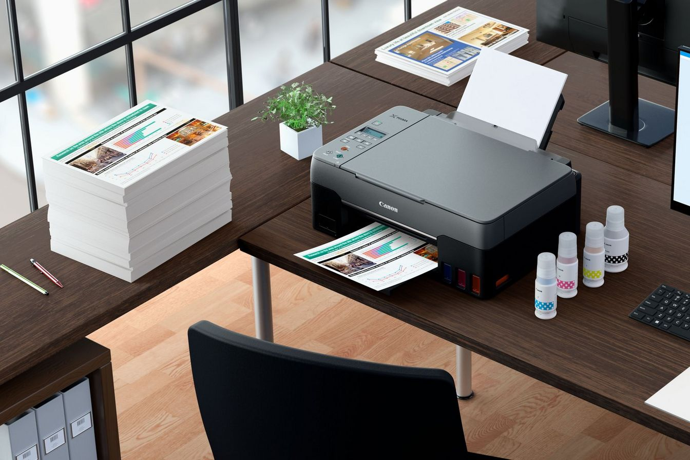 PIXMA G3460 with photo prints and compatible inks in an office desk