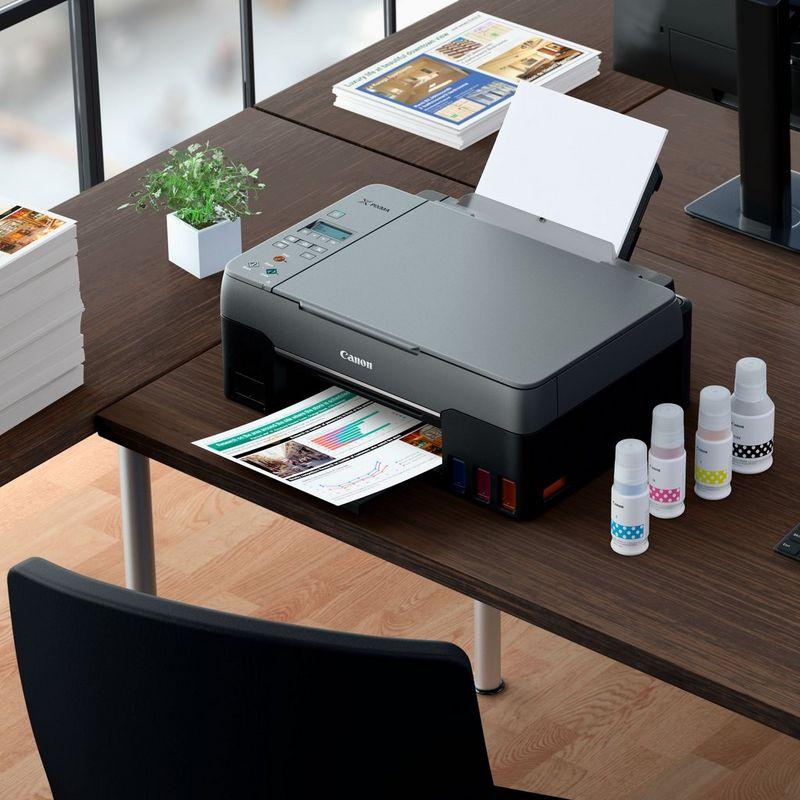 PIXMA G3460 cu fotografii imprimate şi cerneluri compatibile pe un birou