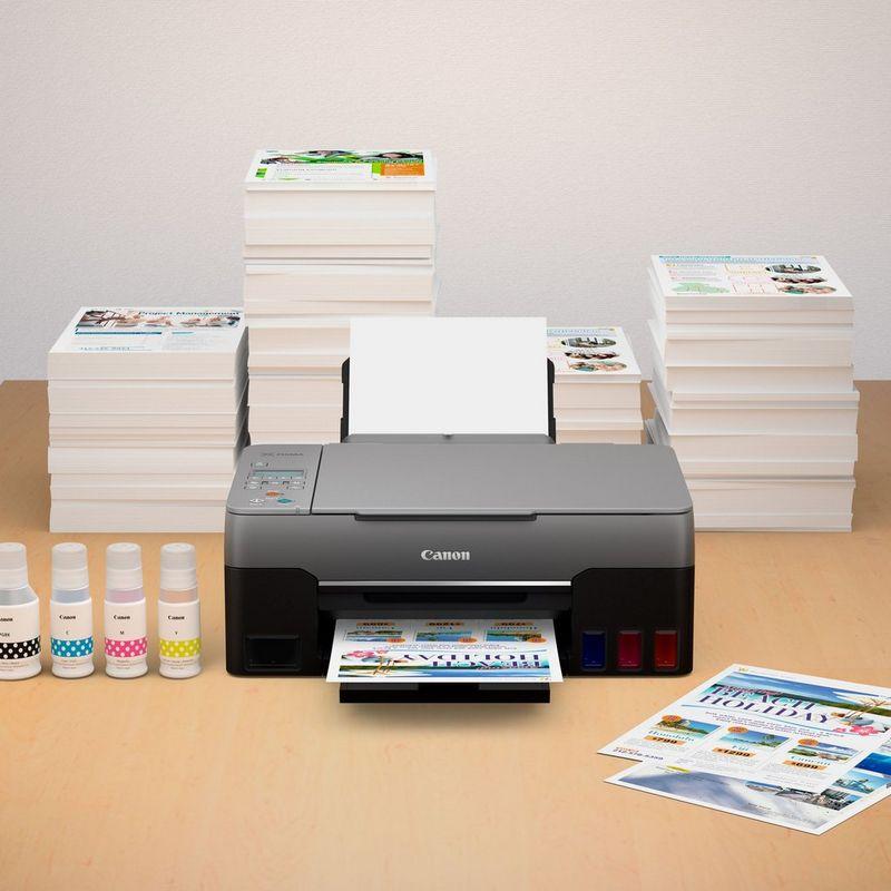 PIXMA G3460 cu un teanc de fotografii imprimate şi cerneluri compatibile pe un birou