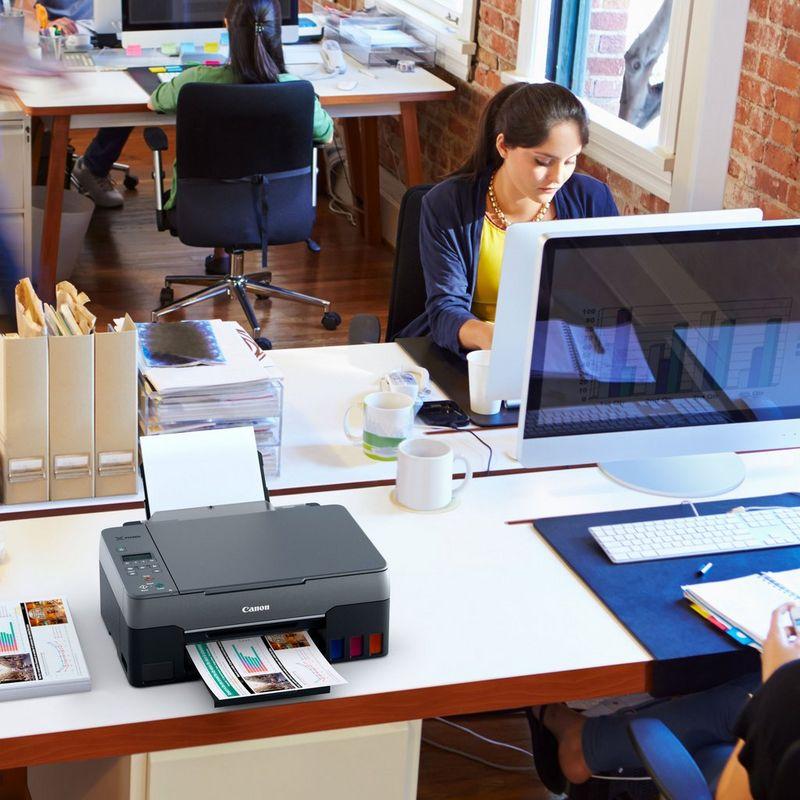 PIXMA G3460 cu fotografii imprimate pe un birou