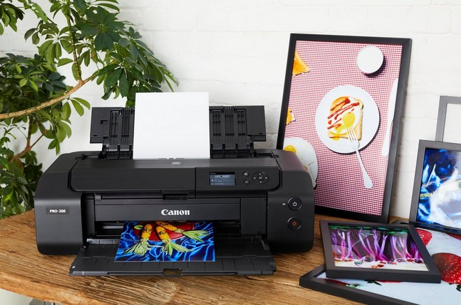 A Canon PIXMA PRO-200 printer on a wooden desk with framed A3 prints surrounding it.
