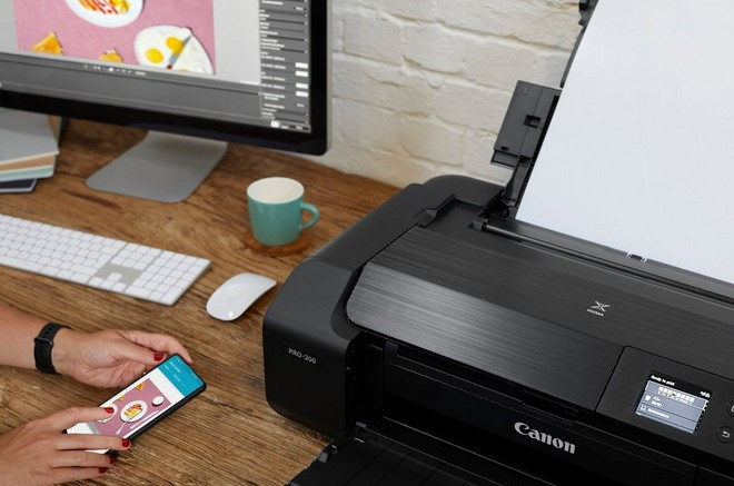 A woman using her smartphone to print on a Canon PIXMA PRO-200 printer.