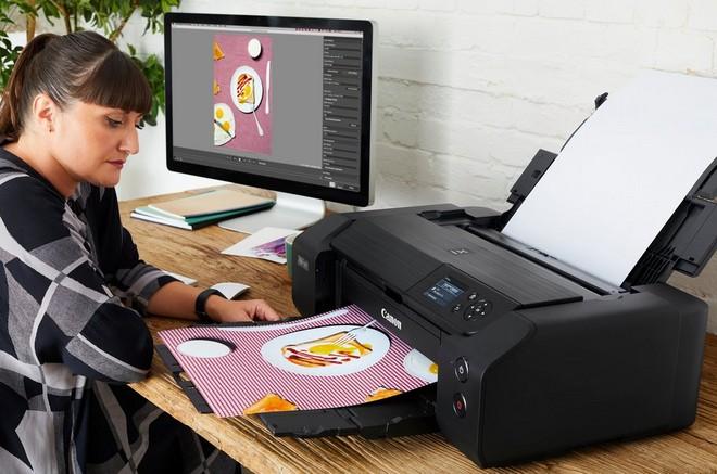 A woman printing a borderless A3 image on a Canon PIXMA PRO-200 printer.