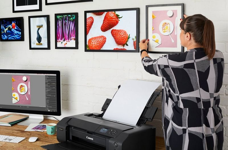 A woman hanging framed photo prints on a wall. On her desk are a computer and a Canon PIXMA PRO-200 printer.