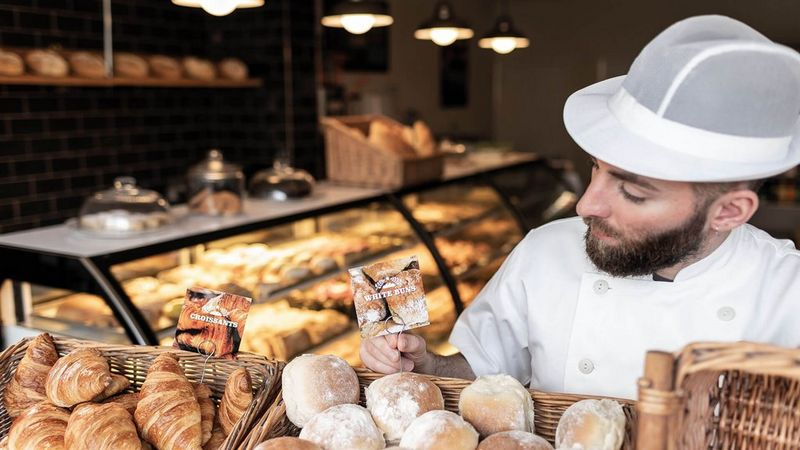 Man at bakery stall surrounded by pastries in basket