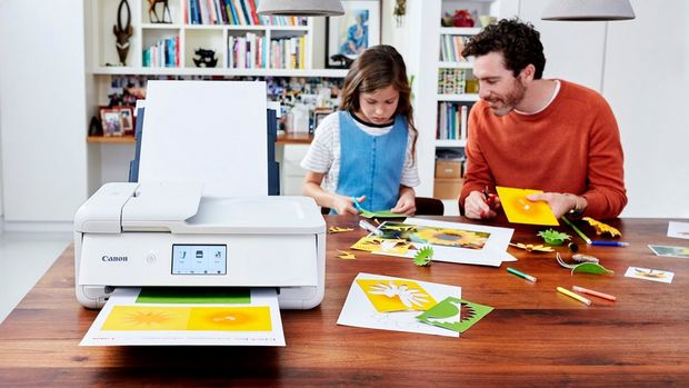 A father helps his daughter make greeting cards out of photographs printed with PIXMA TS 9551C.