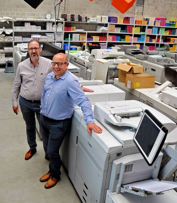 Two men stand next to a large printer